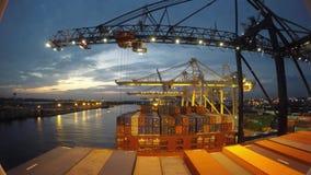 Le gru automatiche nel porto del porto scaricano i contenitori da una nave del trasporto nel colpo di lasso di tempo 4k archivi video