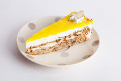 Le gâteau de noix avec le morceau de glaçage jaune de couche sur des points de polka de plat Provence a isolé le fond blanc Photo libre de droits