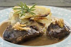 Le guance della carne di maiale in sugo con i porri e la cipolletta caramellati agglutinano Fotografia Stock