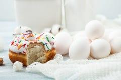 Le guarnizioni di gomma piuma con glassa su una tavola bianca, uova bianche, menu di concetto di Pasqua, concetto di ricetta del  fotografia stock libera da diritti