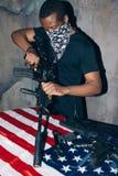Le guerrier noir nettoie son fusil Images stock