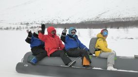 Le guide conduit le motoneige tirant le long bateau de banane gris de neige banque de vidéos