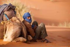 Le guide de chameau de Berber fait une pause Maroc photos stock