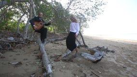 Le guitariste flirte avec la fille blonde qu'elle s'assied sur la branche banque de vidéos