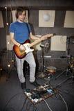 Le guitariste joue près du dispositif de multi-effets Image stock