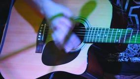 Le guitariste tient la guitare acoustique au concert dans le club clips vidéos