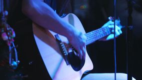 Le guitariste tient la guitare acoustique près du microphone au concert dans le club banque de vidéos