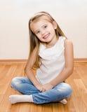 Le gulligt liten flickasammanträde på golv arkivbilder