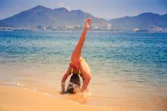 le gymnaste blond dans le bikini dans le pont étire la jambe sur la plage Photo libre de droits