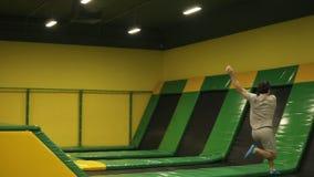 Le gymnaste masculin s'exerce sur le trempoline professionnel, ressorts au-dessus de la barrière avec la torsion de corps et aprè clips vidéos