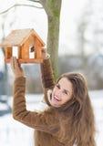 Le hängande fågelförlagematare för ung kvinna på tree Arkivbilder