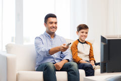 Le hållande ögonen på tv för fader och för son hemma fotografering för bildbyråer