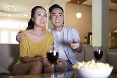 Le hållande ögonen på TV för par på soffan royaltyfria bilder