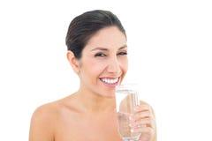 Le hållande exponeringsglas för brunett av vatten och att se kameran Royaltyfri Foto