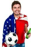 Le hållande fotboll för man och den bärande amerikanska flaggan för ölflaska Royaltyfria Bilder