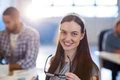 Le hållande glasögon för affärskvinna på kontoret royaltyfri bild