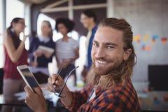 Le hållande glasögon för affärsman och den digitala minnestavlan med kollegor i bakgrund royaltyfria foton