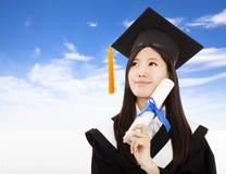 Hållande grad för doktorand- kvinna med molnbakgrund Arkivfoto