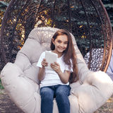 Le hållande vit minnestavlaPC för caucasian flicka, sammanträde i PA Arkivfoton