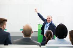 Le höga affärsmanGiving Presentation To kollegor royaltyfri bild