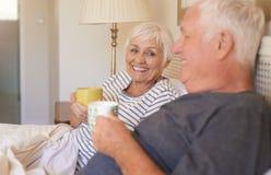 Le höga par som tillsammans dricker kaffe i säng Arkivbild