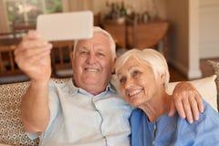 Le höga par som tillsammans tar mobiltelefonselfies på deras soffa royaltyfri fotografi