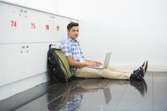 Le högskolestudentsammanträde på golvet med bärbara datorn arkivfoto