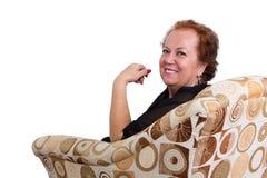 Le högt kvinnasammanträde på soffan Royaltyfri Foto