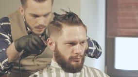 Le hairstyling des hommes et haircutting avec la tondeuse dans un salon de coiffure ou un salon de coiffure banque de vidéos