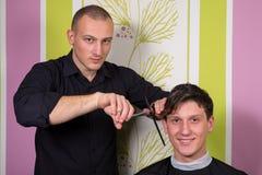 Le hairstyling des hommes et haircutting avec la tondeuse et les ciseaux images stock