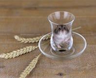 Le hamster dans un becher en verre sur une surface en bois avec du blé égrappe Photographie stock libre de droits