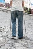 Le handicapé marche en parc sur des béquilles Image libre de droits