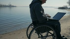 Le handicapé physique se repose sur le fauteuil roulant, nature sur le bord de mer près de la rivière banque de vidéos