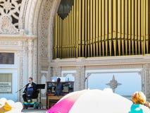 Le handicapé s'asseyant sur le fauteuil roulant chante sur l'étape avec l'organe photos libres de droits