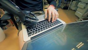 Le handicapé travaille avec un ordinateur portable, fin  banque de vidéos