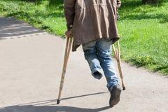 Le handicapé unijambiste marche en parc sur des béquilles Photo stock