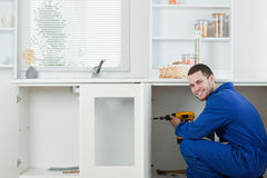 Le handyman som reparationr en dörr royaltyfri fotografi