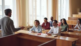 Le haut maître d'école expérimenté parle aux étudiants gais tandis que les jeunes écoutent, sourient et rient banque de vidéos