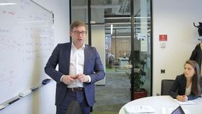 Le haut-parleur se tient devant le tableau noir d'assistance avec des inscriptions d'affaires banque de vidéos