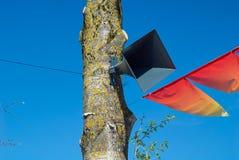 Le haut-parleur sur l'arbre sur le fond du ciel bleu et des drapeaux rouges de vacances Images stock