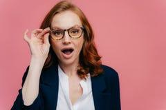 Le Headshot de la femme d'une chevelure rouge étonnée garde la main sur le cadre des verres, mâchoire a laissé tomber, ne peut pa image libre de droits