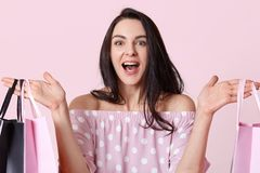 Le Headshot de la jeune femme d'une chevelure foncée heureuse tient des sacs à provisions, regarde joyeux, se réjouit le beau jou images stock