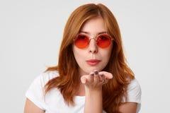 Le Headshot du beau jeune féminin souffle le baiser d'air à vous, utilise les lunettes de soleil élégantes, flirts avec l'ami bel photo libre de droits