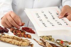 Le herboriste asiatique effectuent une prescription. Photo stock