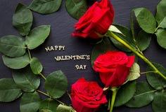 Le ` heureux de Valentine de ` d'inscription sur un fond noir avec les roses rouges Photographie stock libre de droits