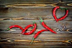 Le hili de ¡ de Ð poivre sur une surface en bois de brun Des deux grains de poivre coeur plié Images libres de droits