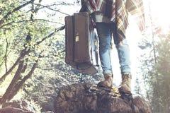 Le hippie avec la valise voyage dans les montagnes Image stock