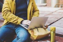 Le hippie avec le sac à dos jaune, veste, chapeau, café de boissons de tasse thermo, travaillent en indépendants utilisant la rue photographie stock libre de droits