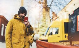 Le hippie avec le sac à dos jaune, veste, le chapeau, café de tasse thermo se tenant dans le smartphone de mains, travaillent en  images libres de droits