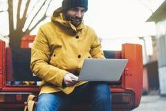 Le hippie avec le sac à dos, la veste jaune et le chapeau se reposant sur la rétro voiture rouge, travaillent en indépendants uti image stock
